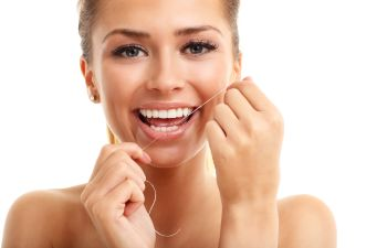 woman flossing her teeth Johns Creek, GA
