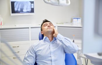 man with a toothache on the dentist chair Johns Creek, GA