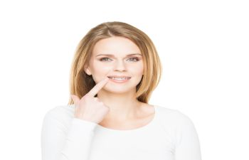 Woman Pointing at Her Smile While Wearing Invisalign BracesJohns Creek GA